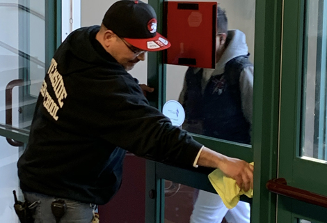 Riverside High School custodian wiping down the door handle to the principal's office.
