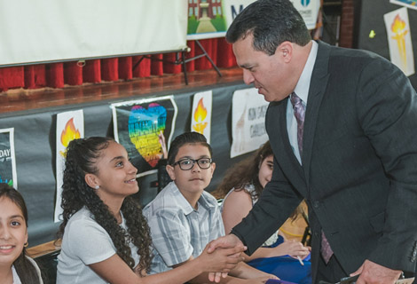 Superintendent of School Dr. Edwin M. Quezadashaing hands with one of the Gibran School students.