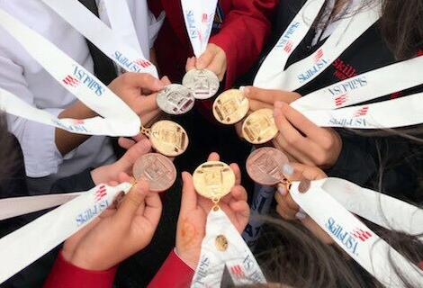 The hands of SkillsUSA students are shown holding the medals won at the competition.