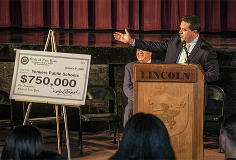 Superintendent of Schools stands with ceremonial check
